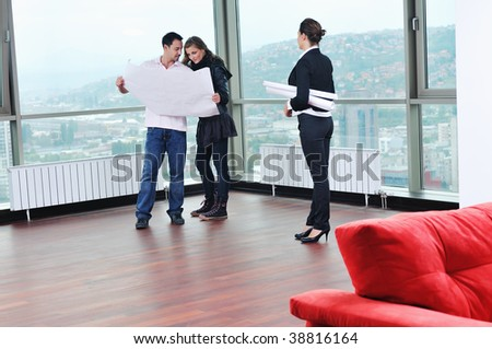 happy young couple buying new home with real estate agent and  looking big comfort bright apartment plans and taking key