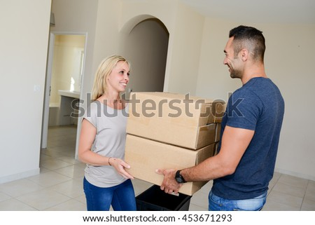 happy young couple carrying cardboard boxes moving into their new house