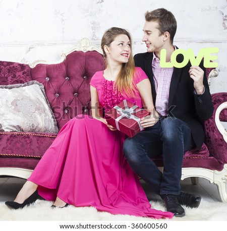 Happy young couple celebrate valentines day sitting on the couch