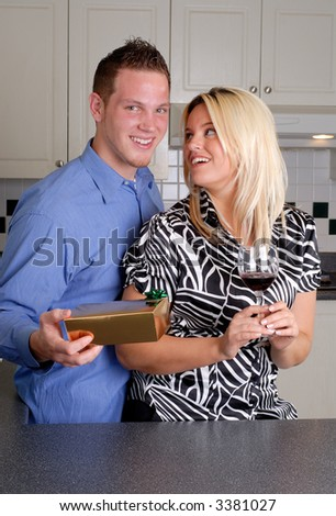 Happy Young Couple Celebrating In The Kitchen, With Gift And Wine