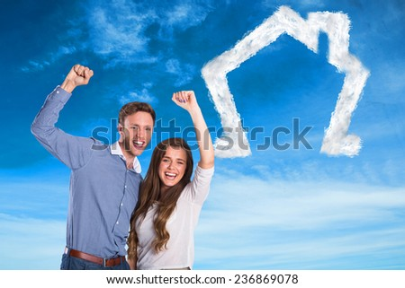 Happy young couple cheering against blue sky - stock photo