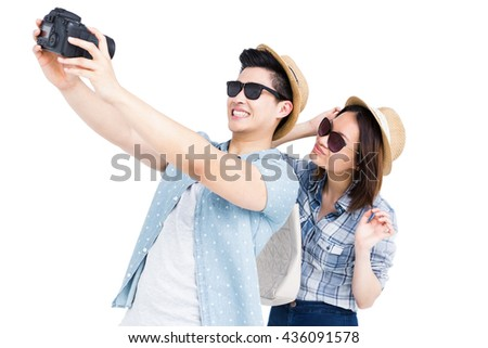 Happy young couple clicking a picture from camera on white background - stock photo
