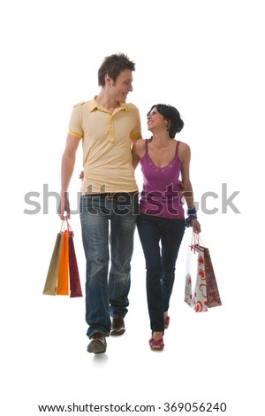 Happy young couple coming back from shopping against isolated white background.