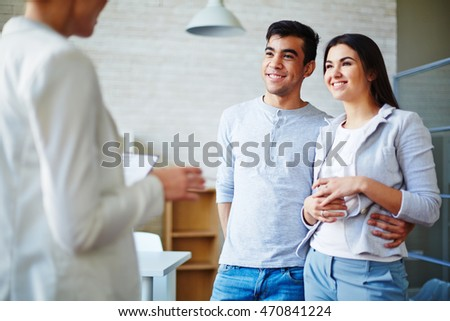 Happy young couple communicating with realtor