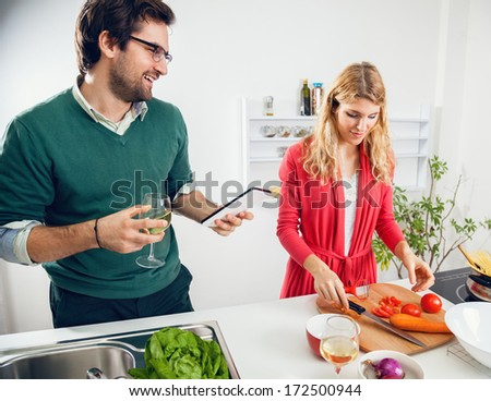 Happy young couple cooking together in kitchen. They are reading the recipe using tablet. - stock photo