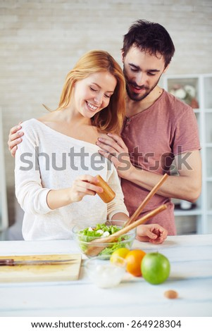 Happy young couple cooking vegetarian salad in the kitchen - stock photo