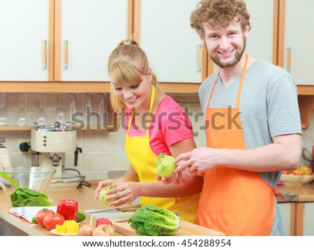 Happy young couple cooking. Woman and man having fun in modern kitchen indoor at home while preparing fresh vegetables food salad - stock photo