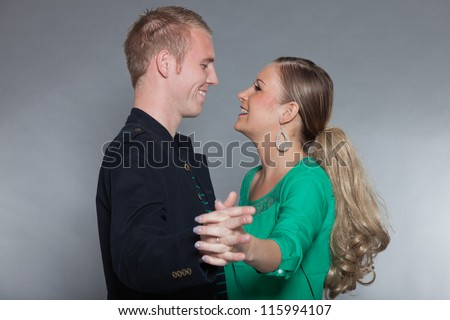 Happy young couple dancing together. Cool looking. Chic dressed. Dark jacket. Green shirt. Jeans. Man short blonde hair. Woman long brown hair. Studio shot isolated on grey background.