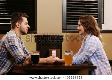 Happy young couple dating in pub - stock photo
