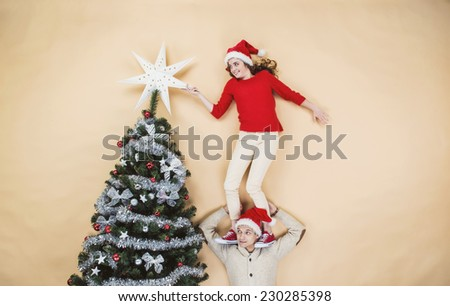 Happy young couple decorating Christmas tree against the beige background - stock photo