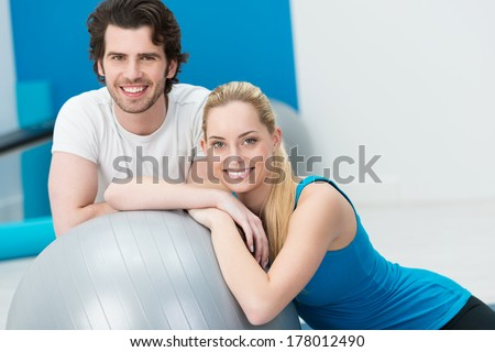 Happy young couple doing fitness training at a gym posing with a large silver gym ball smiling at the camera - stock photo