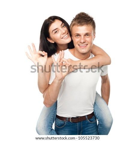 Happy young couple doing Ok gesture, isolated on white background - stock photo