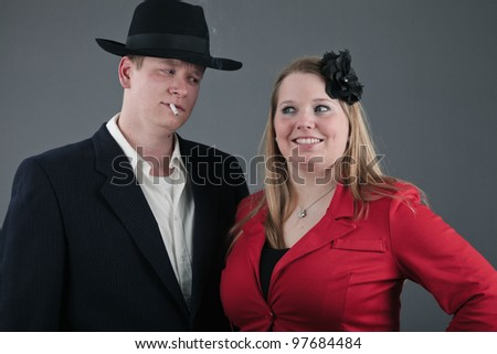 Happy young couple dressed in black and red isolated on grey background