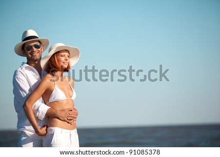 happy young couple, dressed in white, standing on a beach, smiling, holding each other