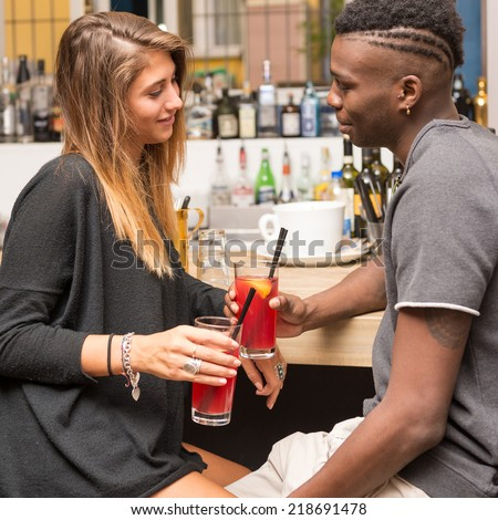 Happy young couple drinking a cocktail in a bar.