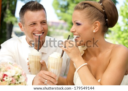 Happy young couple drinking ice coffee through straw on wedding-day outdoors. Laughing happy. - stock photo