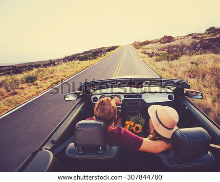 Happy Young Couple Driving Along Country Road in Convertible at Sunset - stock photo