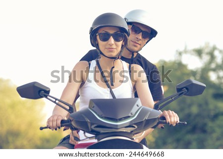 Happy young couple driving scoote - stock photo