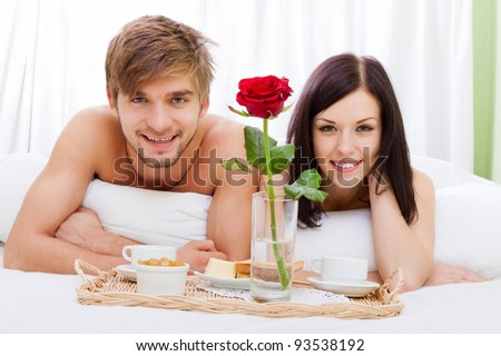 happy young couple eat breakfast in bed in morning with red rose flower, lovely couple lying in a bed, happy smile looking at camera, concept of honeymoon, valentine day - stock photo