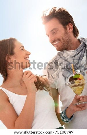 Happy young couple eating icecream together at summer, smiling.? - stock photo