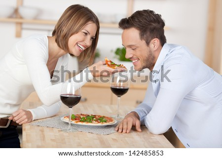 Happy young couple eating pizza with red wine at the kitchen