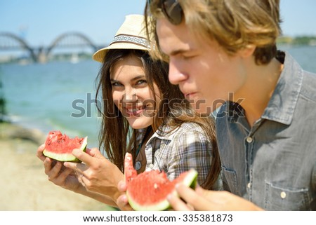 Happy young couple eating watermelon on the beach. Youth lifestyle. Happiness, joy, friendship, holiday, beach, summer concept. Group of young people having fun outdoor.