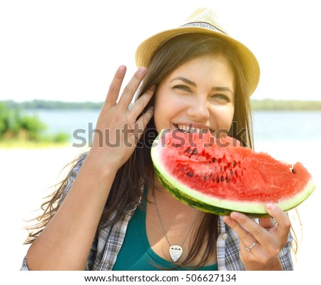 Happy young couple eating watermelon on the beach. Youth lifestyle. Happiness, joy, holiday, beach, summer concept. Group of young people having fun outdoor. Enjoy life, youth and summer.