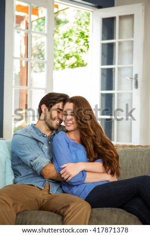 Happy young couple embracing each other in living room - stock photo