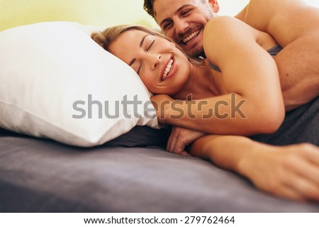 Happy young couple embracing while lying next to each other on bed. Caucasian couple smiling in bed together. Couple waking up. - stock photo