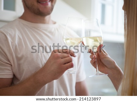 Happy young couple enjoying a glass of white wine at the kitchen