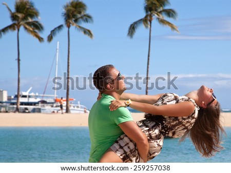 Happy young couple enjoying a romantic day on the Waikiki beach. Couple having fun on romantic travel honeymoon vacation, summer holidays romance. Hawaii, United States Island of Oahu