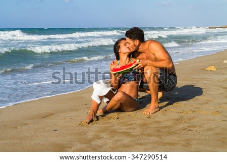 Happy young couple enjoying  a summer dusk  at the beach,  walking barefoot, sharing  a slice of watermelon ,  getting wet, and teasing one another. - stock photo