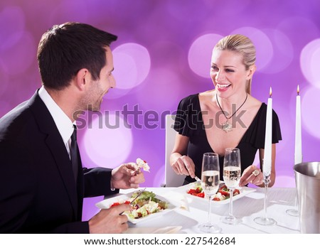 Happy young couple enjoying candlelight dinner at restaurant table - stock photo