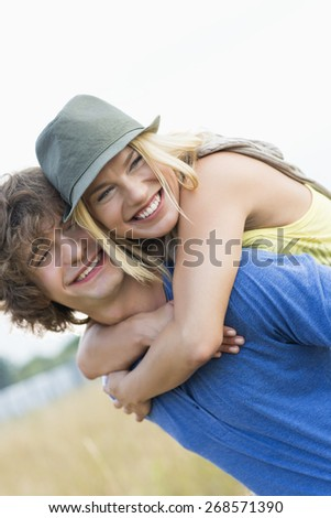 Happy young couple enjoying in field - stock photo