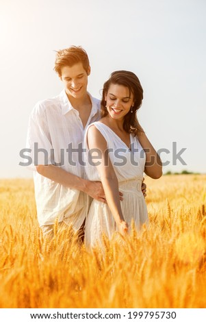 Happy young couple enjoying in the wheat field, summer season .Sunset light, flare light - stock photo