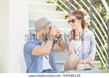 Happy young couple enjoying their summer vacation. They are sitting on the outdoor steps while young man is taking photo of his beautiful girlfriend.  - stock photo