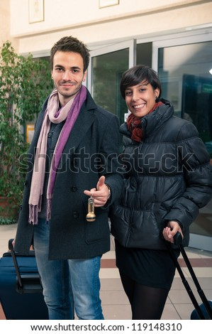 Happy young couple entering in hotel with key of the room. - stock photo