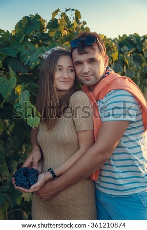 Happy young couple expecting baby, pregnant woman with husband touching belly. Happy and young pregnant couple hugging in nature - stock photo