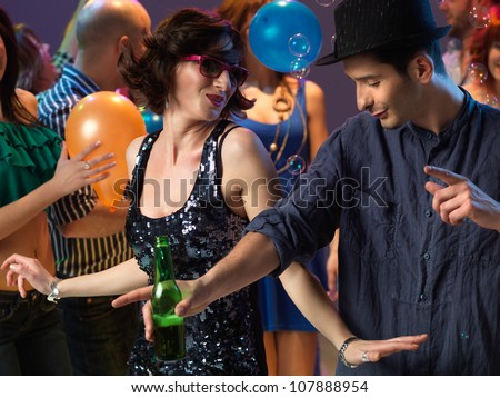 happy, young couple flirting and dancing on the dancefloor in a night club - stock photo