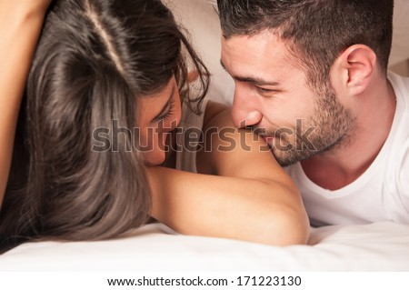 Happy young couple flirting in hotel room. - stock photo
