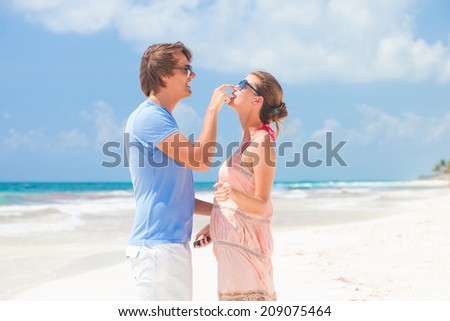 happy young couple flirting on tropical beach