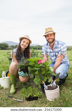 Happy young couple gardening together on a sunny day - stock photo