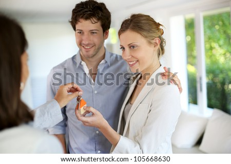 Happy young couple getting keys of their new home - stock photo
