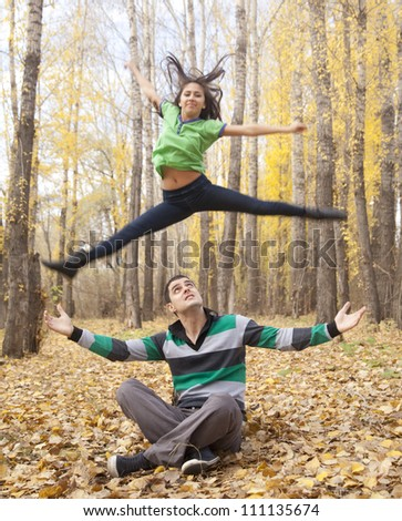 Happy Young Couple - girl  jumping in the sky above  yellow trees