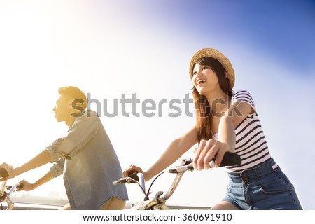 Happy young couple going for bicycle ride on a sunny day