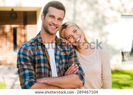 Happy young couple. Happy young couple bonding to each other and smiling while standing against their new house  - stock photo