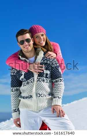 Happy young couple has fun on fresh snow at beautiful winter sunny day on vacation - stock photo
