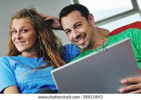 happy young couple have fun and relax at comfort bright apartment and work on laptop computerhappy young couple have fun and relax at comfort bright appartment and work on laptop computer - stock photo