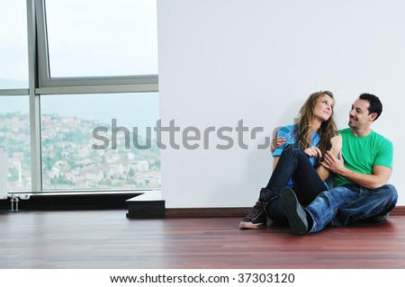 happy young couple have fun and relax in their new big bright home apartment - stock photo