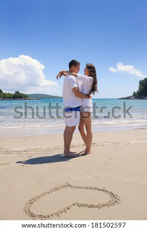 happy young couple have fun and relax  on the summer with heart drawing on beach sand